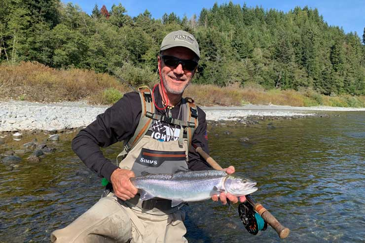 An angler with a wild steelhead on the Klamath